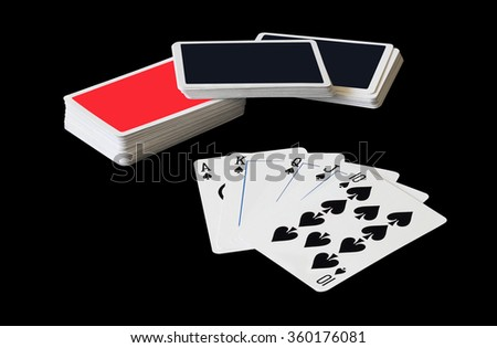 Stacks of playing cards and Royal Flush of spade in poker game isolated on black background, (with clipping path) - stock photo