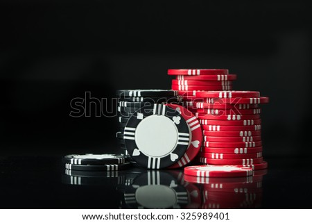 Stacks of poker chips isolated on black background - stock photo