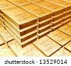 Stacks of pure gold bars on piles of bullion - stock photo
