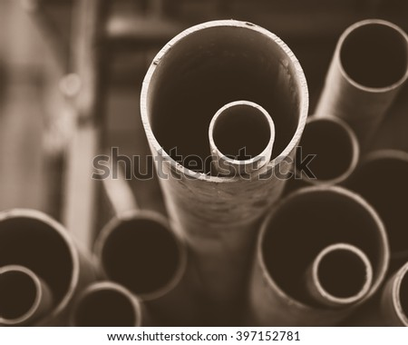 Stacks of PVC water pipes. Abstract circular water pipe. Selective focus. Mononchrome image. - stock photo
