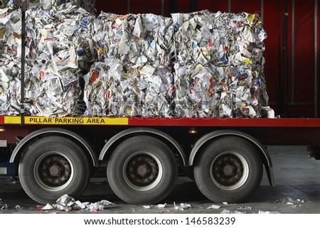 Stacks of recycled papers on lorry in recycling plant - stock photo