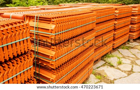 Stacks of red tiles associated with warehousing and transportation, to build a house. The roof of a modern tiled roof covering the house. Tile on the building pallets stacked in standard packaging