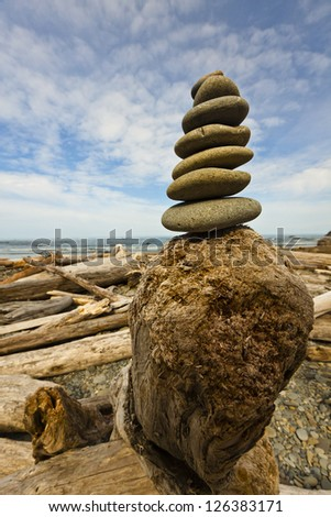 Stacks of Rocks built near the sea on Driftwood - stock photo