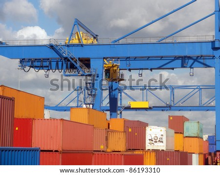 Stacks of shipping containers and fragment  of two crane - stock photo