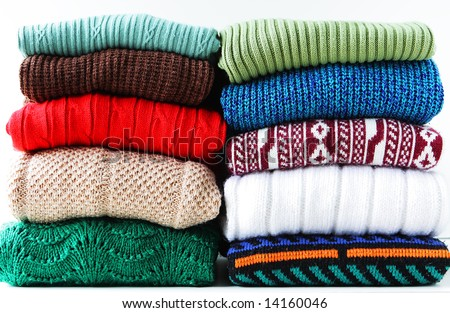 Stacks of sweaters isolated on white - stock photo