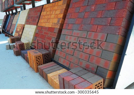 Stacks of various  and for sale. Building and construction materials, colored concrete pavers (paving stone) or patio blocks organized on pallets for sale stored on metal shelves outdoors. - stock photo