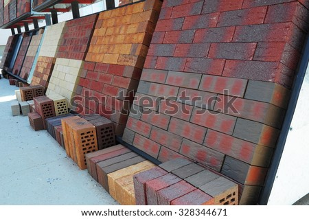 Stacks of various and for sale. Building colorful construction materials, colored concrete pavers (paving stone) or patio blocks organized on pallets for sale stored on metal shelves outdoors.  - stock photo