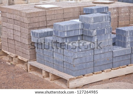 Stacks of various colored concrete pavers (paving stone) or patio blocks organized on wooden pallets and for sale in a retail setting such as a garden center or building supply. - stock photo
