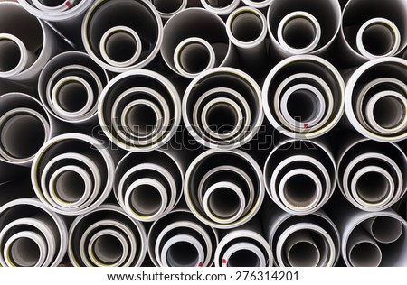 Stacks of white PVC water pipes - stock photo