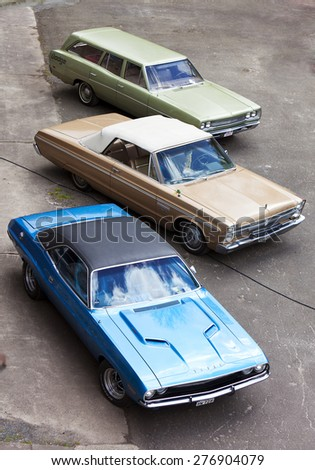 Stade, Germany - May 2, 2015: 1969 Dodge Coronet Station Wagon, 1965 Plymouth Sport Fury Convertible and 1972 Dodge Charger at Spring Fling, annual meeting for vintage cars built by Chrysler Corp. - stock photo