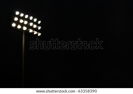 Stadium flood lights on a sports field at night with copy space - stock photo