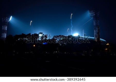 Stadium floodlights against a dark night sky background - stock photo