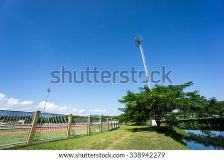 Stadium lamp in the blue sky - stock photo