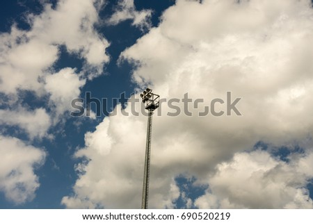 stadium light pole with sky and clouds