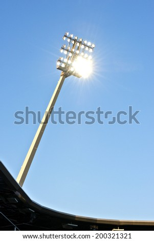 Stadium lights at dusk against a blue sky with the lights on - stock photo