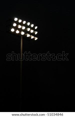 Stadium lights on a sports field at night with copy space - stock photo
