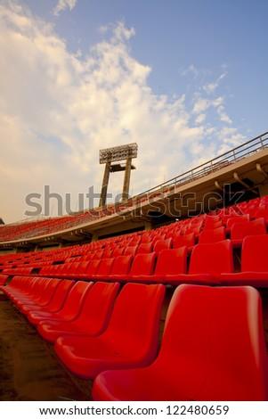 stadium, red seats on stadium steps bleacher with spot light pole - stock photo