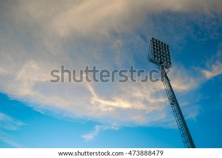 Stadium spotlights with blue sky and white cloud