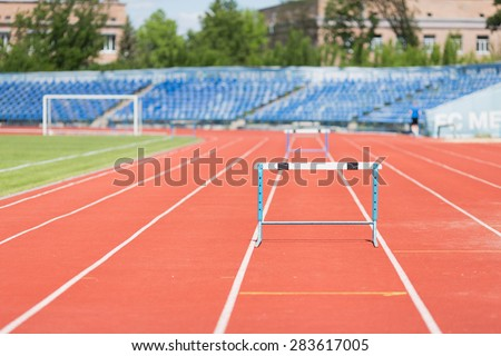 Stadium treadmill.Photo treadmill with a barrier in an empty stadium during the day - stock photo