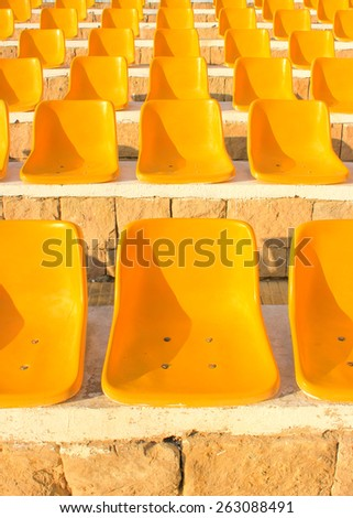 Stadium Yellow Chairs at sun light. - stock photo