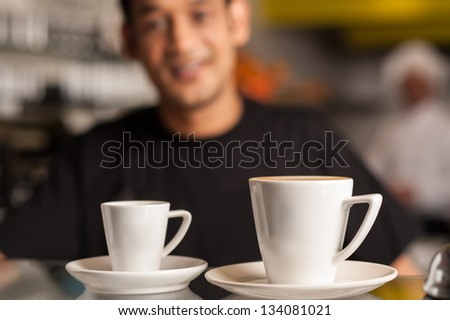 Staff at cafe serving coffee. Blurry background.