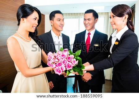 Staff greeting guests in hotel - stock photo