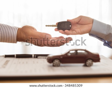 Staff handed the car keys to the client. Concept of car insurance, rental, sales. - stock photo