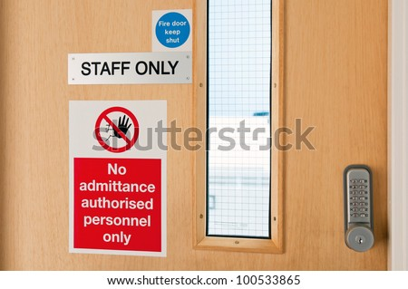staff only door signs outside laboratory room with security door lock keypad