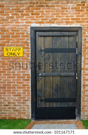 Staff only room with brick wall and old retro interior entrance door design - do not enter without authorization warning badge label