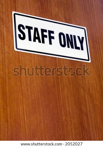 STAFF ONLY signage on a wooden door