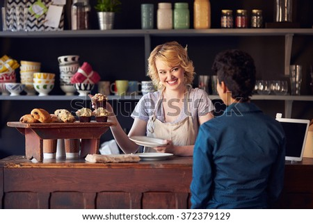 Staff Serving Customer In Busy Coffee Shop - stock photo