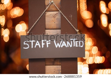 Staff wanted inscription on a board hanging on wooden post with blurred lights on background - stock photo