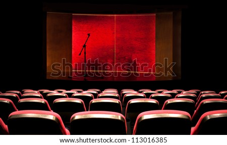 stage with microphone in front of empty seats - stock photo
