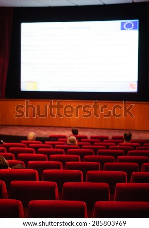 Stage with podium and big screen. People at conference hall, rear view - stock photo