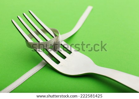 Stages of tying bow on fork on green background, close-up