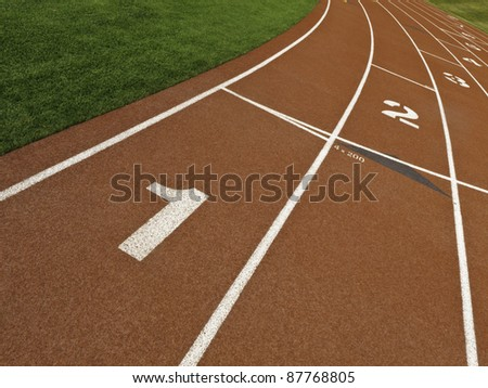 Staggered lane numbers on rubberized surface of all-weather running track - stock photo