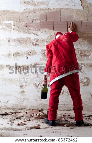 Staggering Drunken Santa Holding on a Wall - stock photo