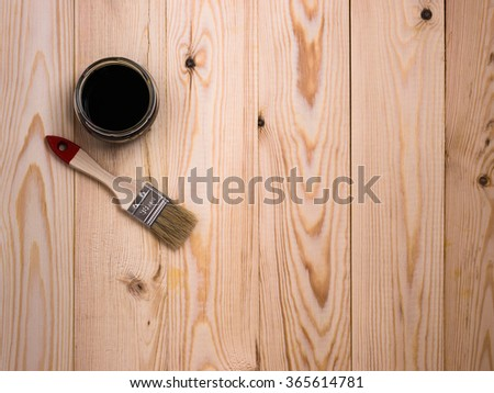 stain and brush on wooden backdrop - stock photo
