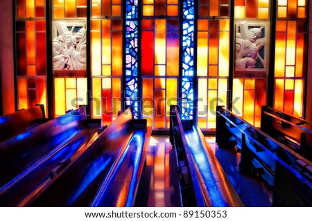 stain glass reflections reflected off of church pews - stock photo