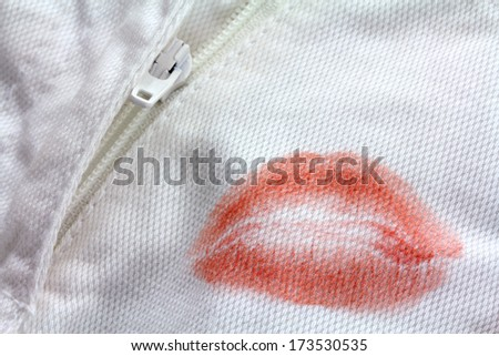 Stain of Red Lipstick kiss near a zipper on a white pants - stock photo