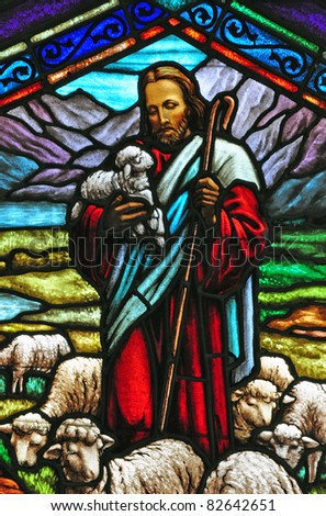 Stained glass church window showing Jesus with lambs - stock photo
