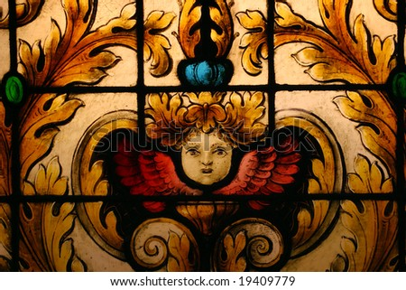Stained glass depicting face of cherub angel - stock photo