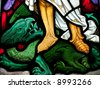 Stained glass in Catholic church showing victory over satan - stock photo
