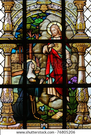 Stained glass window depicting a nun kneeling for Christ.