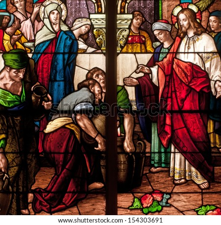 Stained glass window depicting Bible story of wedding feast of Cana, Jesus turning water into wine - stock photo