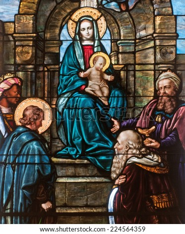 Stained glass window depicting Christmas scene of the adoration of the magi with Mary holding the child Jesus - stock photo