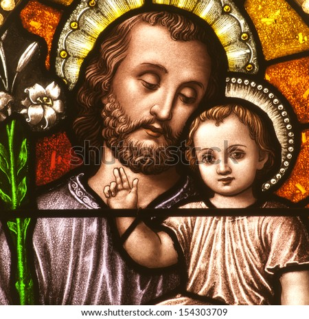 Stained glass window depicting closeup of Saint Joseph with the child Jesus - stock photo
