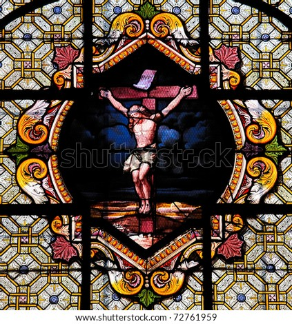 Stained Glass window depicting Jesus Christ on the cross in the Saint Sulpice church in Paris - stock photo