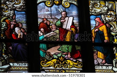Stained glass window depicting Moses showing the Stone Tablets with the Ten Commandments. This window is located in Saint James's Church in Stockholm. It was fabricated in 1893. - stock photo
