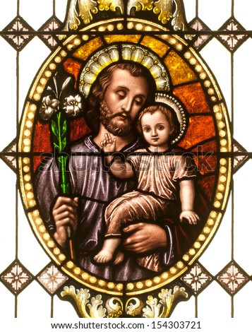Stained glass window depicting Saint Joseph holding the child Jesus - stock photo